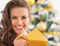 Jovem mulher de sorriso com o envelope na frente da árvore de Natal imagem de stock royalty free
