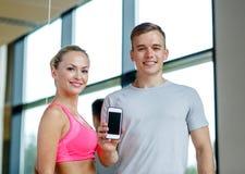 Jovem mulher de sorriso com o instrutor pessoal no gym imagem de stock