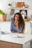 Jovem mulher de sorriso com o portátil na cozinha em Fotos de Stock Royalty Free