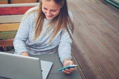 Jovem mulher de sorriso com o smartphone e o portátil que trabalham no café fora, no freelancer e no local de trabalho foto de stock