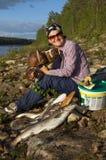 A jovem mulher de sorriso com os presentes da natureza senta-se no banco do rio do norte Fotos de Stock
