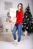 Jovem mulher de sorriso com os presentes de um Natal e a árvore de Natal Fotografia de Stock