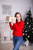 Jovem mulher de sorriso com os presentes de um Natal e a árvore de Natal Fotos de Stock