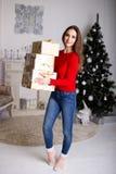 Jovem mulher de sorriso com os presentes de um Natal e a árvore de Natal Foto de Stock Royalty Free