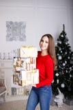 Jovem mulher de sorriso com os presentes de um Natal e a árvore de Natal Fotografia de Stock Royalty Free