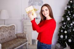 Jovem mulher de sorriso com os presentes de um Natal e a árvore de Natal Fotos de Stock Royalty Free