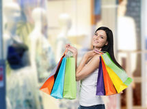 Jovem mulher de sorriso com os sacos de compras coloridos das lojas extravagantes Foto de Stock