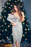 A jovem mulher de sorriso com presente de Natal encaixota perto da árvore de Natal Feriados, celebração e povos imagens de stock