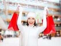 Jovem mulher de sorriso com sacos de compras vermelhos Fotografia de Stock Royalty Free