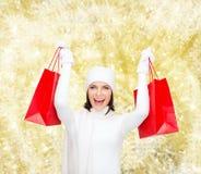 Jovem mulher de sorriso com sacos de compras vermelhos Imagens de Stock