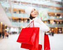 Jovem mulher de sorriso com sacos de compras vermelhos Imagem de Stock Royalty Free