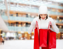 Jovem mulher de sorriso com sacos de compras vermelhos Fotos de Stock