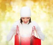 Jovem mulher de sorriso com sacos de compras vermelhos Imagem de Stock