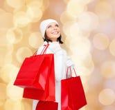 Jovem mulher de sorriso com sacos de compras vermelhos Imagens de Stock Royalty Free