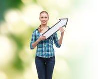 Jovem mulher de sorriso com a seta que poiting acima Foto de Stock Royalty Free