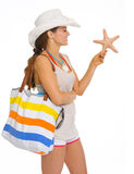 Jovem mulher de sorriso da praia que guardara a estrela do mar Imagem de Stock Royalty Free