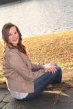 Jovem mulher de sorriso em escadas pela água Imagem de Stock Royalty Free