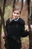 A jovem mulher de sorriso em um revestimento preto no outono estaciona imagens de stock