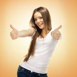 A jovem mulher de sorriso feliz com polegares levanta o gesto Fotografia de Stock Royalty Free