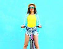 A jovem mulher de sorriso feliz do verão monta uma bicicleta Imagem de Stock
