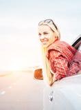 A jovem mulher de sorriso feliz olha para fora da janela de carro Foto de Stock