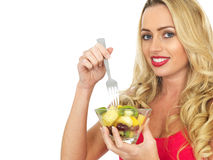 Jovem mulher de sorriso feliz que come a salada de fruto fresco Imagem de Stock Royalty Free
