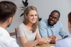 Jovem mulher de sorriso feliz que fala com os colegas de trabalho no trabalho fotos de stock royalty free