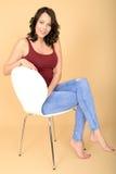 Jovem mulher de sorriso feliz que senta-se em uma cadeira branca que relaxa Imagem de Stock