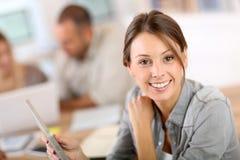 Jovem mulher de sorriso na classe de treinamento que usa a tabuleta Imagens de Stock