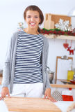 Jovem mulher de sorriso na cozinha, isolada sobre Imagens de Stock