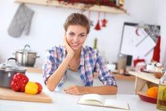 Jovem mulher de sorriso na cozinha, isolada sobre Imagem de Stock