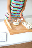 Jovem mulher de sorriso na cozinha, isolada sobre Fotos de Stock Royalty Free