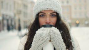 Jovem mulher de sorriso na roupa morna branca com e no café bebendo a levar embora sobre o fundo nevado da cidade video estoque