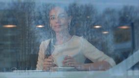 Jovem mulher de sorriso no café com fones de ouvido que escuta a música da tabuleta imagens de stock royalty free