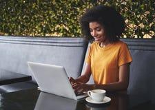 Jovem mulher de sorriso no café que datilografa no portátil fotografia de stock royalty free