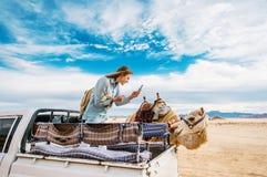 A jovem mulher de sorriso no carro toma a foto do camelo no meio do deserto de Wadi Rum em Jordânia imagem de stock royalty free