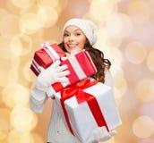 Jovem mulher de sorriso no chapéu do ajudante de Santa com presentes Fotografia de Stock