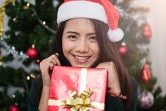 Jovem mulher de sorriso no chapéu do ajudante de Santa com caixa de presente Imagem de Stock