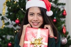 Jovem mulher de sorriso no chapéu do ajudante de Santa com caixa de presente Fotos de Stock