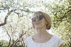 Jovem mulher de sorriso no jardim da mola Fotos de Stock