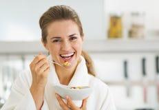 Jovem mulher de sorriso no roupão que come o café da manhã saudável Foto de Stock