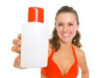 A mulher de sorriso no roupa de banho que mostra o sol obstrui a nata foto de stock royalty free