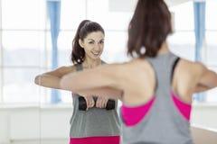 Jovem mulher de sorriso no sportswear com pesos na frente de um espelho no gym imagem de stock royalty free