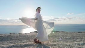 A jovem mulher de sorriso no vestido branco está girando ao redor no penhasco vídeos de arquivo