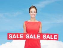 A jovem mulher de sorriso no vestido com venda vermelha assina Fotos de Stock Royalty Free