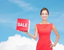 A jovem mulher de sorriso no vestido com venda vermelha assina Fotografia de Stock