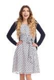 A jovem mulher de sorriso no vestido e no casaco de lã pontilhados branco está olhando acima Imagem de Stock Royalty Free