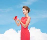 Jovem mulher de sorriso no vestido vermelho com caixa de presente Imagens de Stock Royalty Free