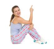 Jovem mulher de sorriso nos pijamas que sentam-se no assoalho imagens de stock royalty free