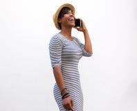 Jovem mulher de sorriso que anda e que fala no telefone celular Fotos de Stock Royalty Free